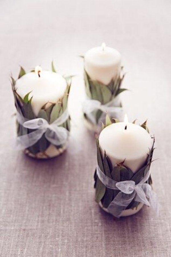 DIY Wedding Decorations like these eucalyptus wrapped candles make the perfect budget centerpiece at your reception