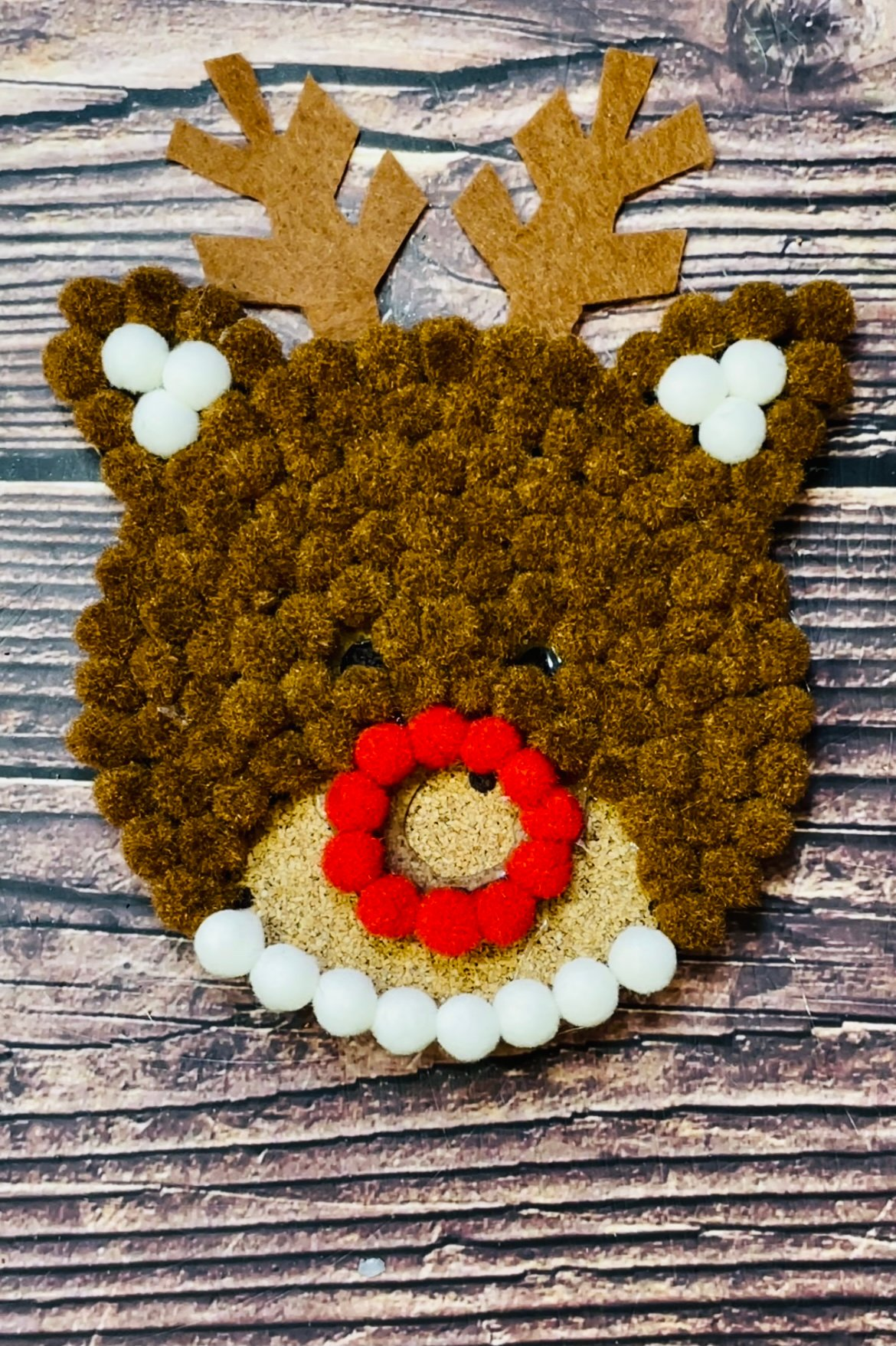 While the outer edge of the red nose sets, secure the bottom edge of cream pom-poms as shown and add some cream pom-poms for the insides of the ears. Doing the outer edges and allowing them to cool will ensure the design retains a good shape whilst you fill in the middle.