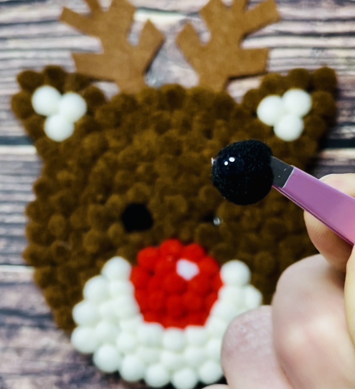 Secure the eyes by adding a drop of hot glue onto each of the black pom-poms and securing them individually... be sure to use tweezers to protect your fingers!