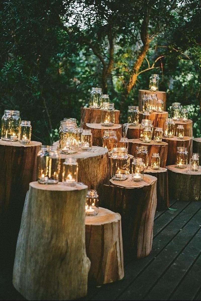 Wedding mason jar ideas like these jars on logs look magical and inviting
