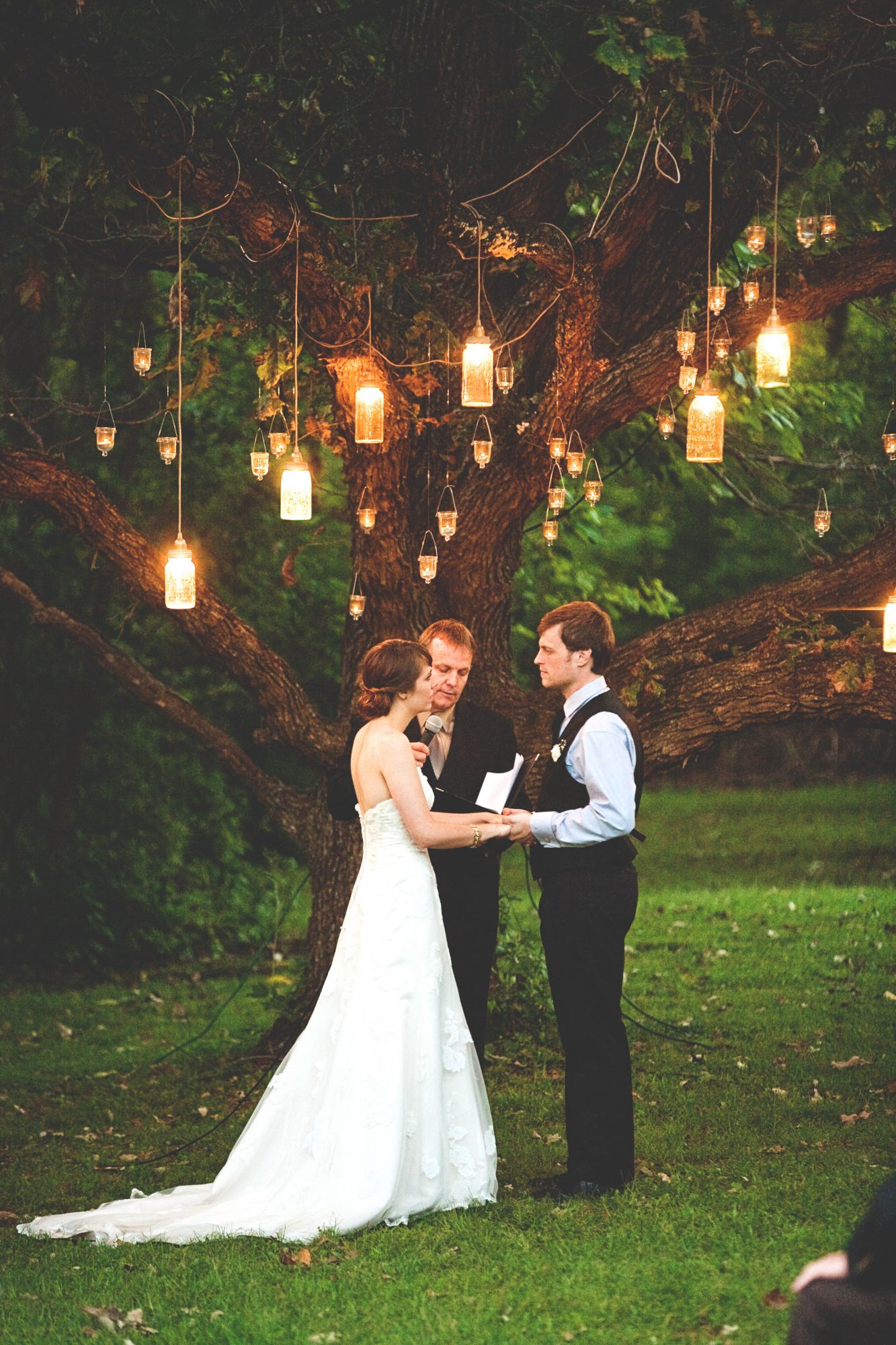 These mason jar lights hanging from a tree are one of our favoritie wedding mason jar ideas