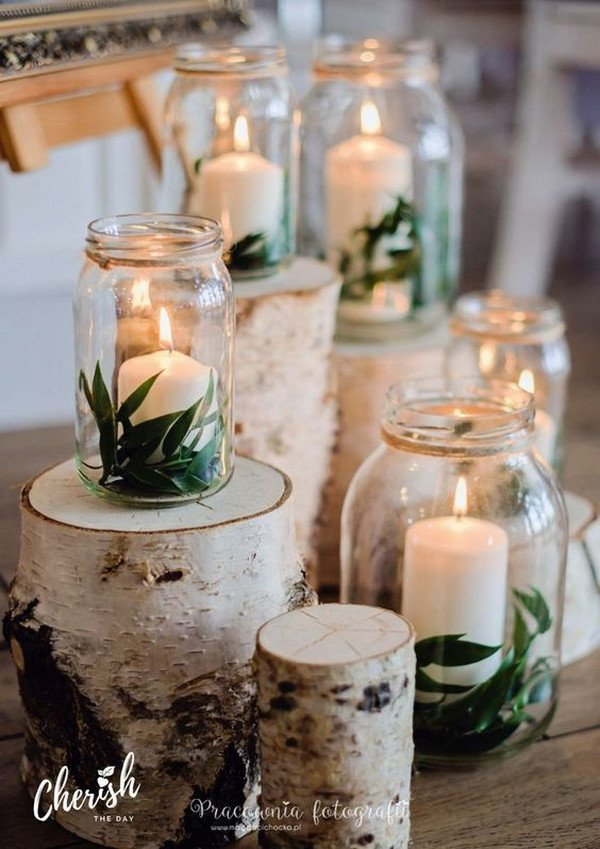 Some wedding mason jar ideas use natural elements like logs to achieve a rustic, warm style that looks stunning