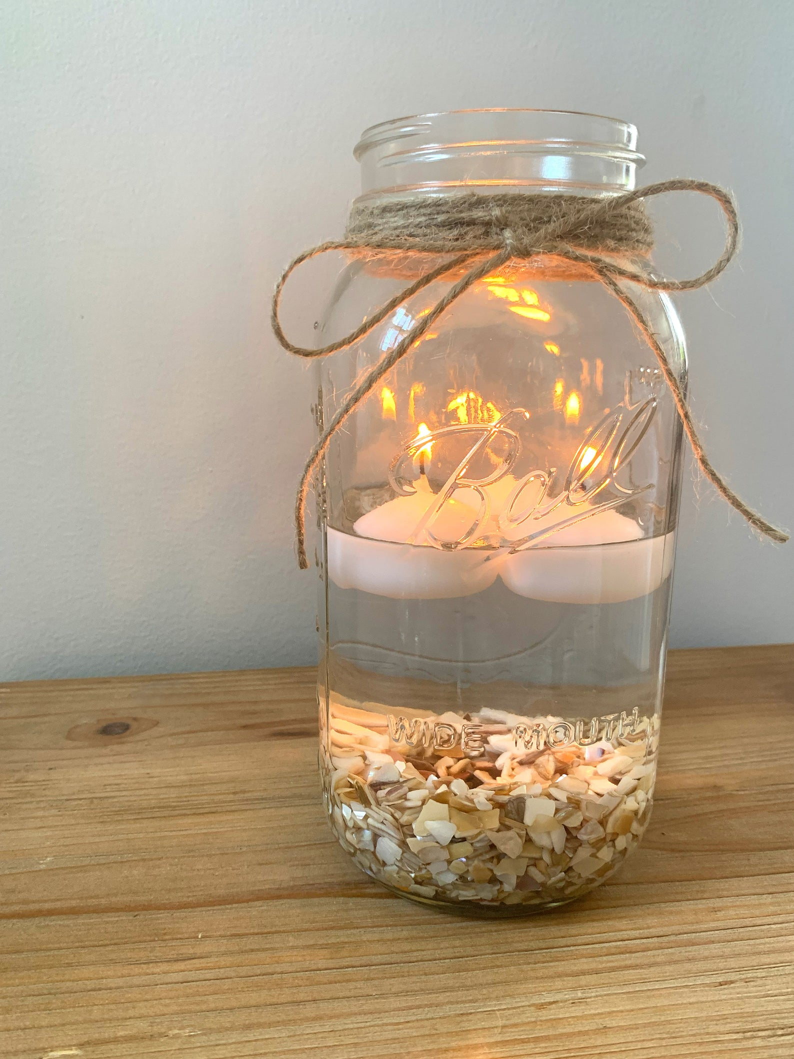 Mason jar with floating candles and shells